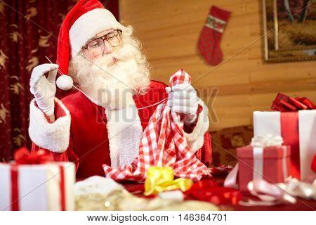 Santa Claus sitting at the table and sewing