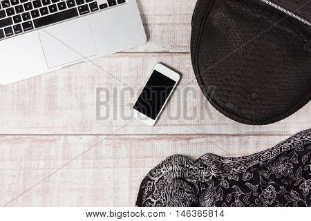 Fashion women accessories. Luxury handmade snakeskin (python) rucksack,  laptop, smartphone. Top view, flat lay, light wooden  background. Free/empty space for text.