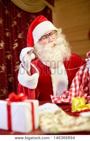 Santa Claus sitting at the table and preparing gifts for Christmas