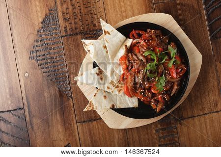 Fajitas with beef and bell pepper in a pan. Wooden background.