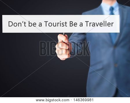 Don't Be A Tourist Be A Traveller - Businessman Hand Holding Sign
