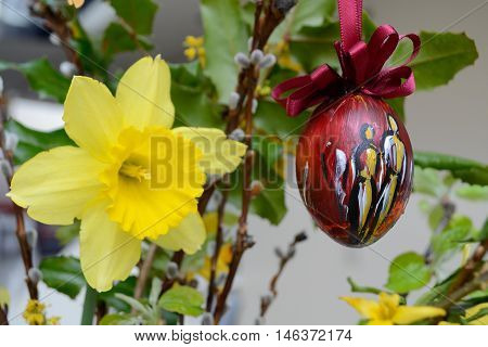 Daffodil and artistically painted Easter egg in flowers