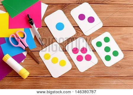 Education flash cards for kids. Learning colours. Teaching kids to count. Scissors, pencil, glue, colored cardboard sheets on a wooden table. How to make flash cards for kids. Step