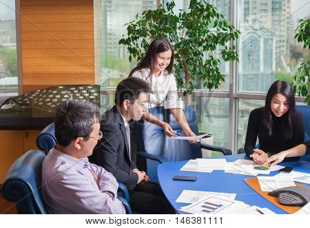 Business meeting Asian people sitting for a glass table with business plan on high floor in the office. Asian nationality male in suit. Asian nationality girl shows a business graph of his business partner.