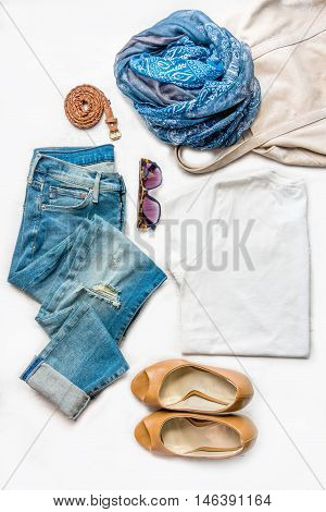 Collage of female clothing set. Ripped jeans white top brown high heels shoes and accessories over white wood background.