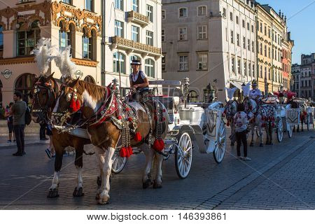 KRAKOW, POLAND - SEP 8, 2016: Old-styled carriage for tourists in the streets of Old Krakow. Krakow is visited by over 8 million tourists a year, number of foreign tourists up to 2 million people.