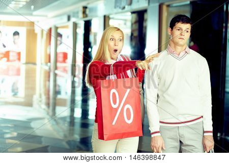 Young woman pointing excitedly at something in the shop standing by her husband