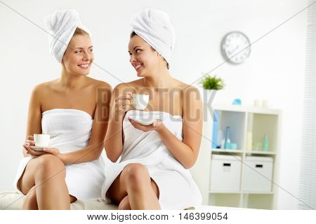 Two young girls drinking tea and communicating at bathhouse poster