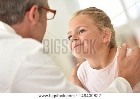 Doctor examining little girl's throat