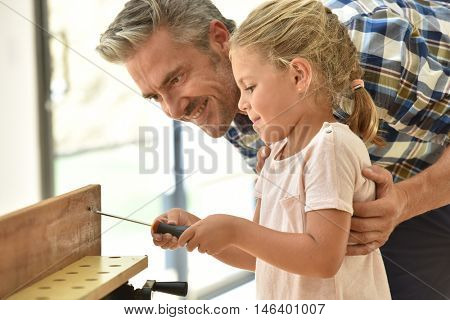 Daddy teaching daughter how to use screwdriver
