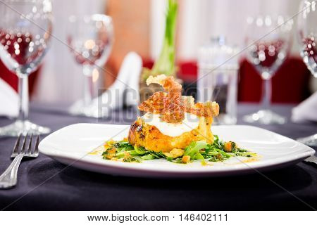Romantic dinner - Beautiful meal of fish with crispy pancetta in a lovely restaurant setting