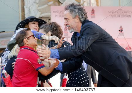 Deep Roy and Tim Burton at the Tim Burton Hand And Footprint Ceremony held at the TCL Chinese Theater in Hollywood, USA on September 8, 2016.