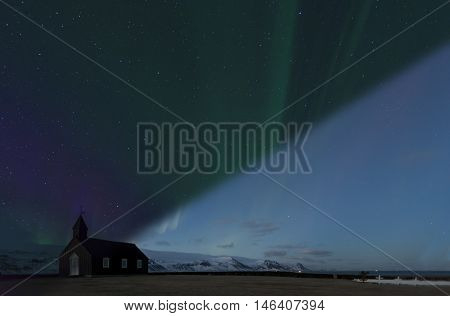 Dramatic Northern Lights Aurora Borealis dancing over the Black Church of Budir in Iceland transition concept of twilight and night
