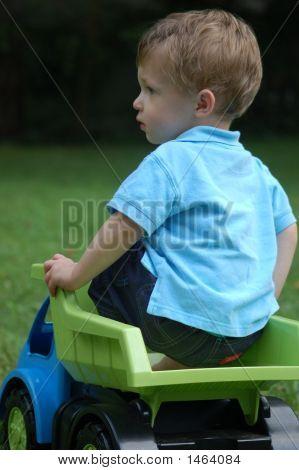 Little Boy In Toy Truck In The Yard
