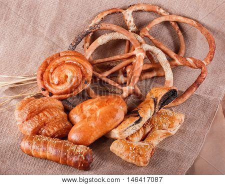 Various Puff Pastry, Croissants, Buns And Pies, Pretzels On Rustic Background With Spikelets. Pastri