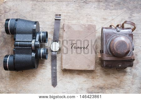 Travel - inscription on an old book and binoculars, watch, retro camera on vintage brown table.