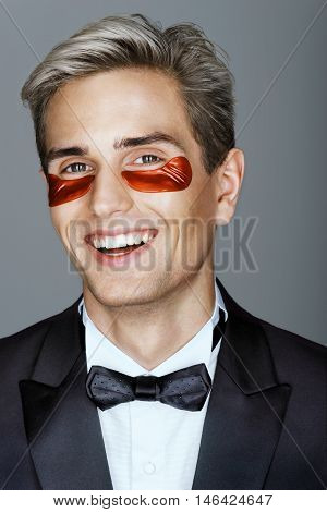 Elegant man with red eye patches. Portrait of smiling man with perfect skin. Grooming himself.