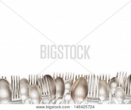 Aged vintage silver forks and spoons border isolated on white background. Fork and spoon background.