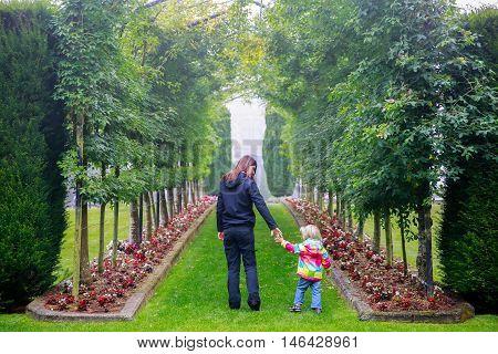 DUNEDIN NEW ZEALAND - FEBR 10 2015: young woman with cute little girl walking in the Garden of Larnach Castle