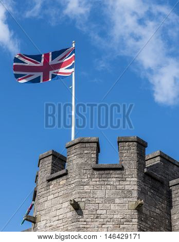 The union flag flying above castle ramparts, against a deep blue sky