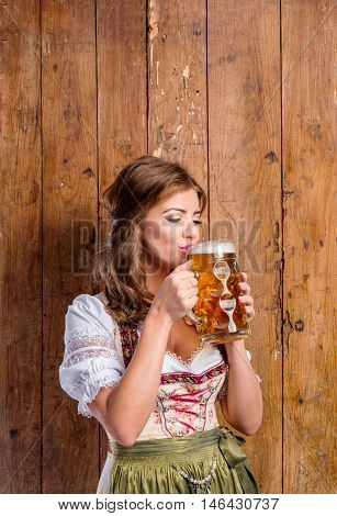 Beautiful young woman in traditional bavarian dress holding a mug of beer, drinking from it. Oktoberfest. Studio shot on brown wooden background. Copy space.