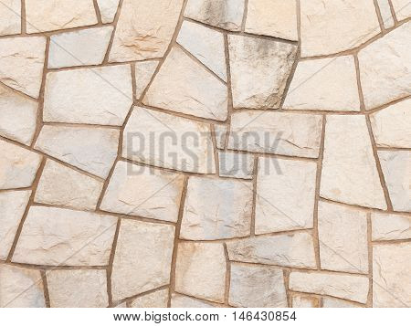 decorative light old rough wall made of natural sandstone with potholes and smudges on the street