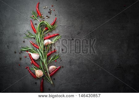 Seasoning background. Rosemary pepper and garlic on dark background. Food ingredients with copy space.