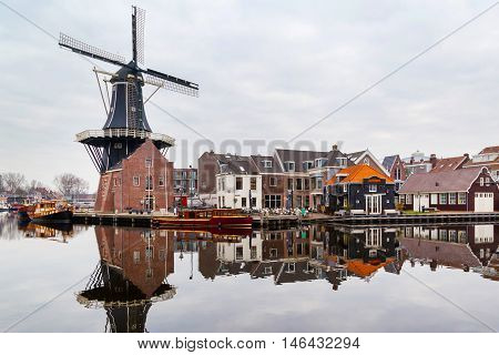 Haarlem, Netherlands - April 2, 2016: Picturesque landscape with the windmill and traditional houses, Haarlem, Holland