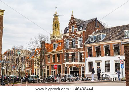 Haarlem, Netherlands - April 2, 2016: Picturesque landscape with people, beautiful traditional houses and church clock tower, Haarlem, Holland