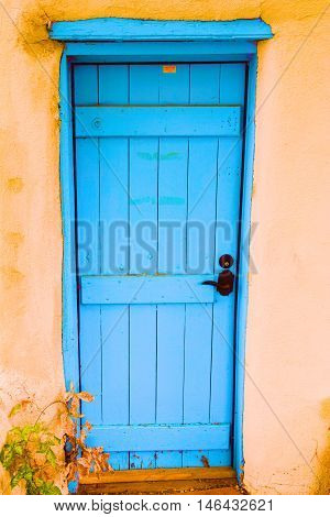 Colorful blue wooden door with a rustic vibe taken in an adobe residential home