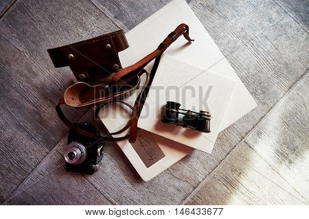 Photobook in bright leather, retro binoculars and old camera. Creative atmosphere