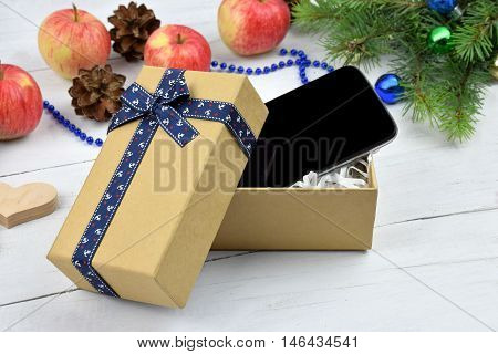 Open Christmas gift box with a smart phone inside presents and apples tree branches and balls all around.A great gift for Christmas. Modern technologies and Christmas wishes. The attributes of modern life. / Listen to the music for the holidays /. Communi