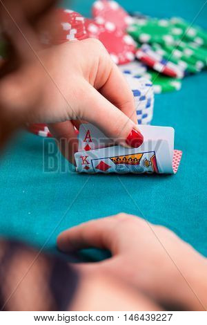 Young woman holding ace and king poker cards in front of gambling chips. Close up detail on cards