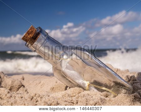 Corked bottle with message stuck in the sand on the beach