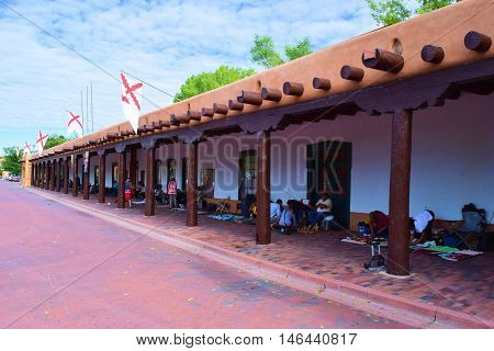 August 29, 2016 in Santa Fe, NM:  Palace of the Governors adobe building built in 1610 which has been a historical government building for centuries and where Native Americans sell and trade merchandise with locals and tourists in the building courtyard