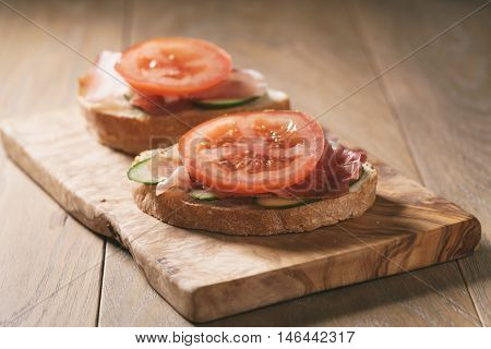 ciabatta open sandwiches with speck and vegetables, shallow focus