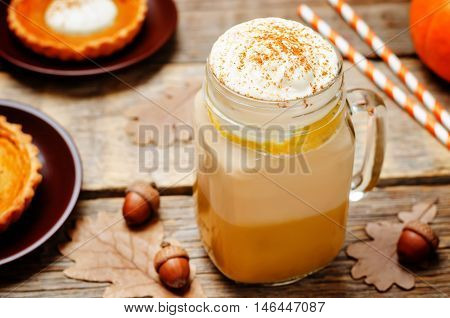 pumpkin pie spice pumpkin latte on wooden background