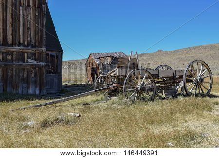 Old Barn, Outhouse, and Wagon: deep blue sky, and a beautiful field, with an old bar, outhouse, and wagon, in the historic ghost town, Bodie