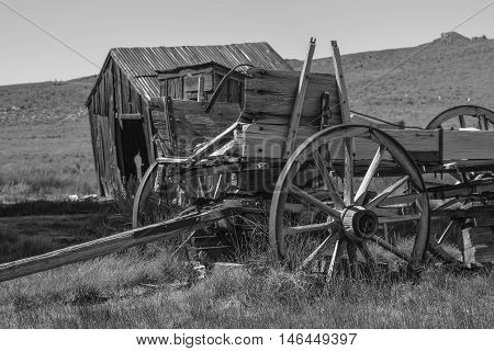 Old Wagon in Black and White: a black and white shot of an old wagon and an outhouse, in the historic town, Bodie