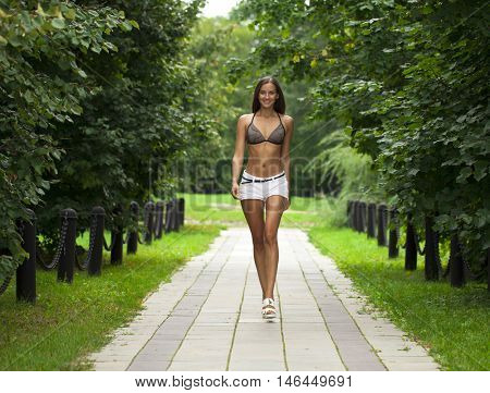 Portrait of young brunette woman in white short walking in summer park