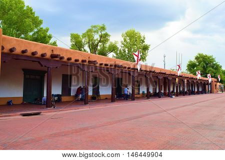 August 29, 2016 in Santa Fe, NM:  Palace of the Governors which is a historic Spanish style adobe building which has been a government building in the past and where Native Americans sell and trade their merchandise in the courtyard taken in Santa Fe, NM