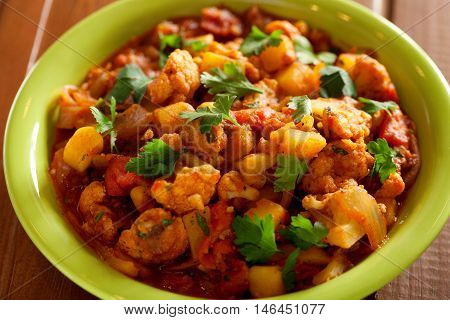 Gobi Aloo is famous Indian curry dish with potatoes and cauliflower. Close up shot over wood