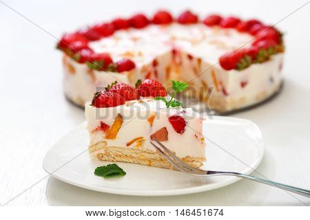 Cake with strawberries gelly yogurt and cherries. Surface view. Isolated on white background. One piece in a white plate