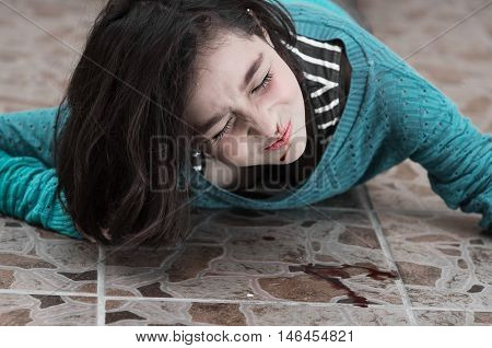 pretty young upset girl with a bleeding nose after falling down