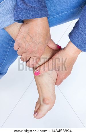 woman holding a foot with painful bunion