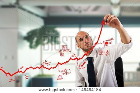 Businessman draw graphics on an arrow uphill