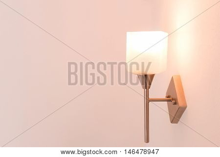 Wall lamp with yellow shade in house.