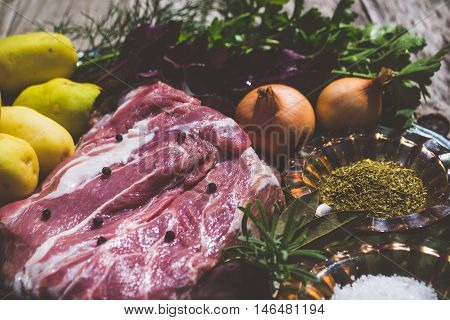 Raw meat and vegetables on woodden background