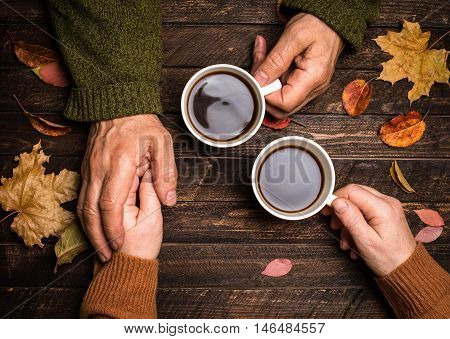 Old people holding hands. Closeup. The senior people hand holding a cup of coffee on wooden rustic table covered with autumn leaves. Old age concept.