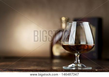 glass of whiskey with ice on a wooden table. brandy.
